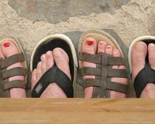 4 Füße im Sand als Zeichen für fremdgehenden Partner